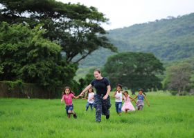 Nicaragua gringo woman running in a field with Nicaraguan children – Best Places In The World To Retire – International Living
